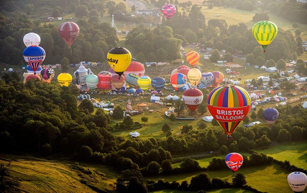 Hot air balloons lift off during a mass ascent at the 36th International Balloon Fiesta at the Ashton Court Estate near Bristol, England.