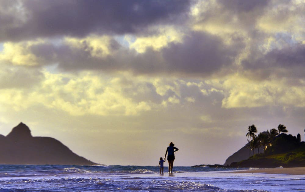 Anne Kllingshirn, of Kailua, Hawaii walks with her daughter Emma, 1, as storm clouds float overhead during the sunrise hours on Kailua Beach, in Kailua, Hawaii.
