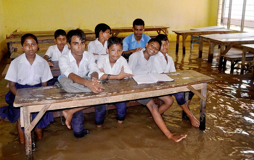 Students inside a waterlogged classroom after a heavy shower in Guwahati.