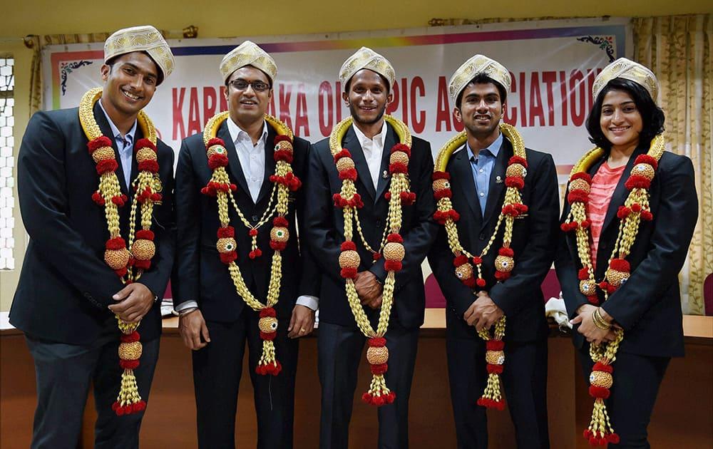 CWG medalists, Prakash Nanjappa (shooting), hockey players V R Raghunath, Nikin thimmaiah, S V Sunil and shuttler Ashwini Ponappa wear Mysore peta during a felicitation programme by Karnataka Olympic Association in Bengaluru.