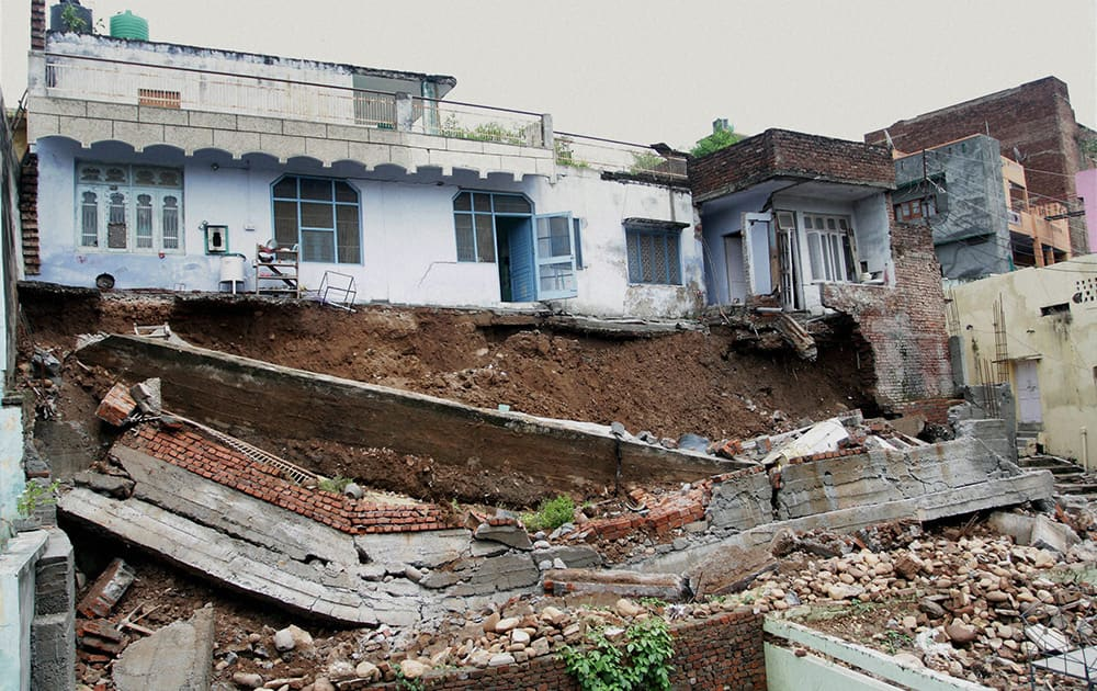 Household goods and appliances lying scattered after a house collapsed near a drain injuring three people in Thane.