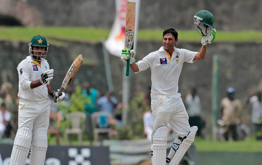 Pakistani cricketer Younis Khan raises his bat after scoring 150 runs as teammate Sarfraz Ahmed applauds during the second day of the first test cricket match between Sri Lanka and Pakistan in Galle, Sri Lanka.