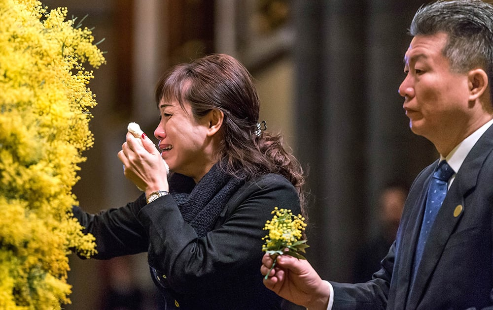 Sprigs of wattle blossoms are placed on a wreath by mourners during a national memorial service for the victims of Malaysia Airlines Flight 17 at St Patrick's Cathedral in Melbourne, Australia.