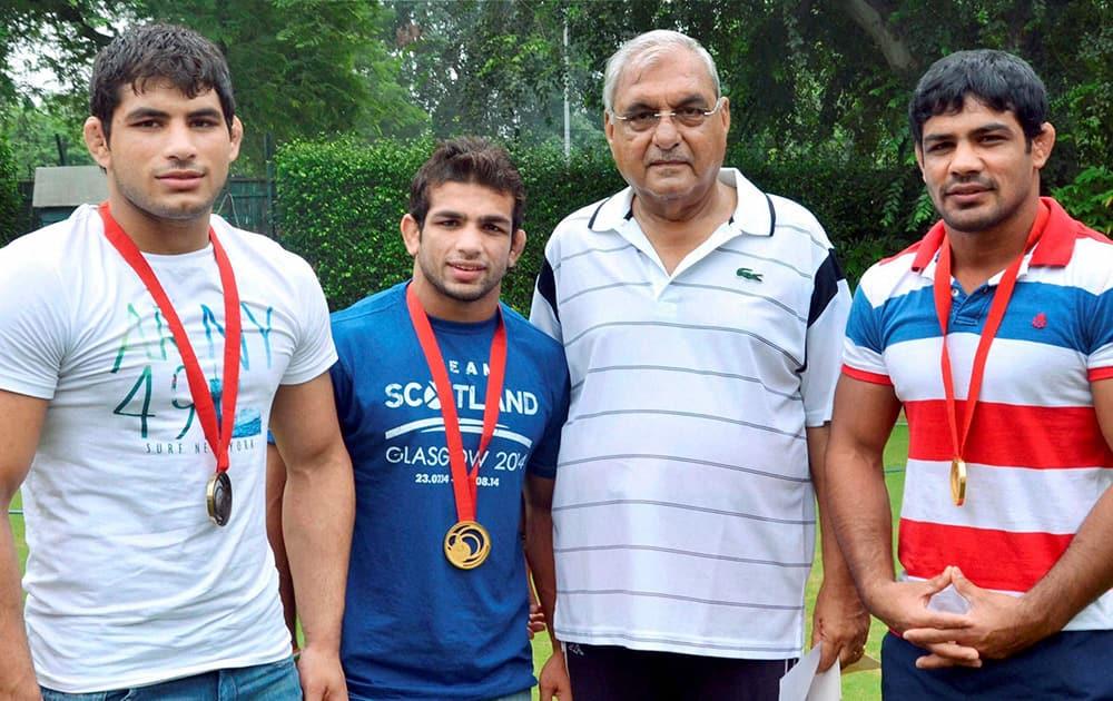 Haryana Chief Minister Bhupinder Singh Hooda with CWG medalists, Sushil Kumar(R), Amit Kumar(L) and Pawan Kumar(2nd L) in New Delhi.