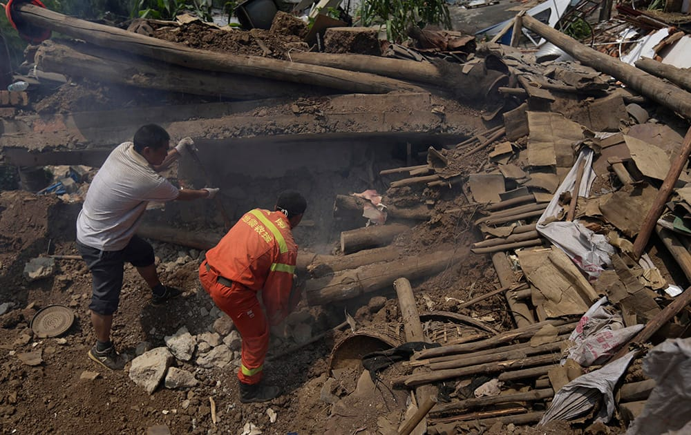 A villager helps a rescuer as they look for missing persons amid the rubble of destroyed houses following an earthquake in the town of Longtoushan in Ludian County in southwest China`s Yunnan Province.