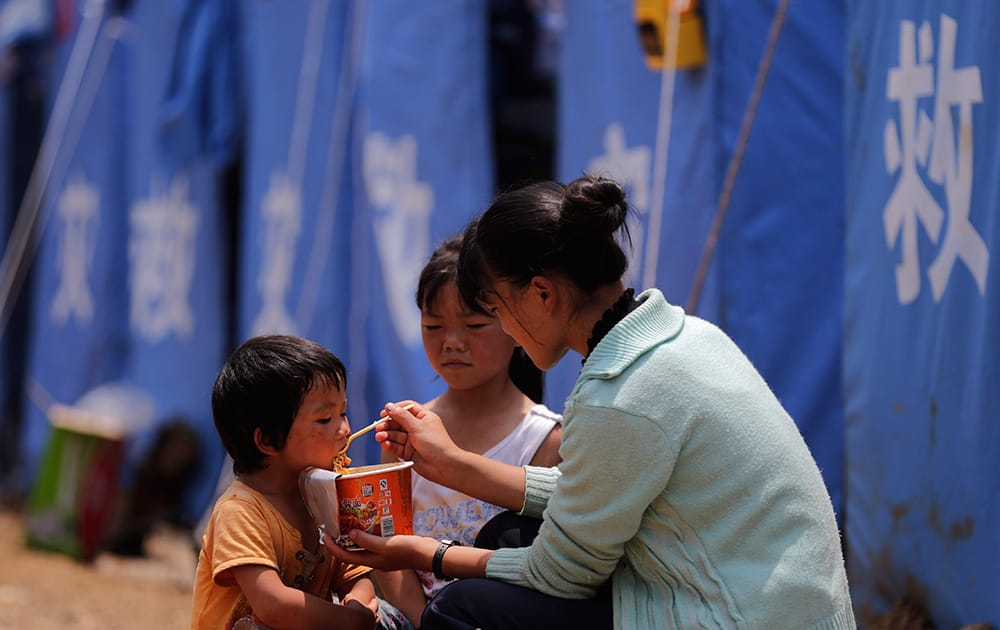 A woman feeds instant noodle to the children outside a temporary tent set up for the earthquake survivors in the town of Longtoushan in Ludian County in southwest China`s Yunnan Province.