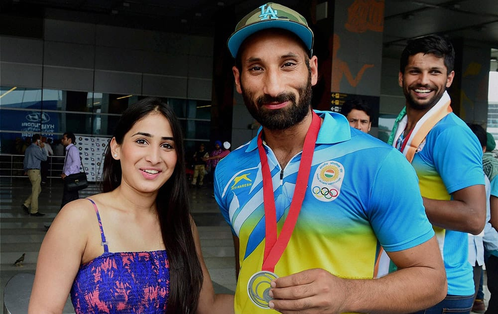 Indian Hockey captain Sardara Singh with his fiancee English Hockey player Ashpal Bhogal on their arrival at the IGI Airport in New Delhi on Tuesday after participating in CWG 2014 at Glasgow.