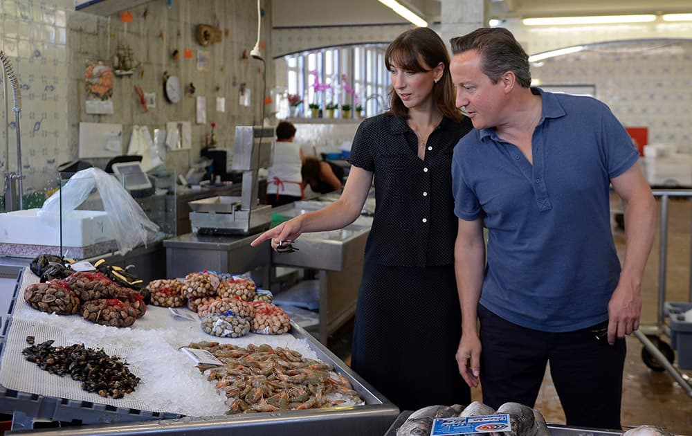 Britain`s Prime Minister David Cameron, right, and his wife Samantha, pose for photos as they a visit a seafood market, during their summer vacation, in Cascais, Portugal.