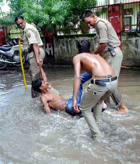 Police arrest students in a waterlogged area during a Chakka Jaam protest by them in Allahabad.