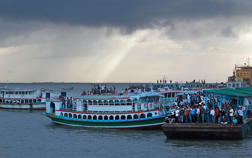 Bangladeshi people gather on the banks of the River Padma after a passenger ferry capsized in Munshiganj district, Bangladesh.