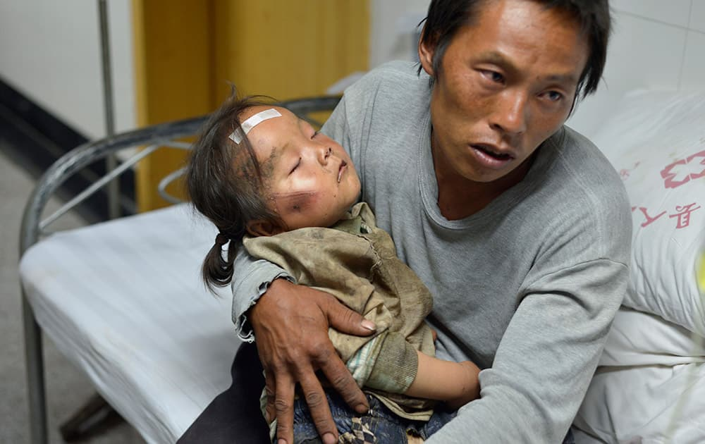 A man holds an injured child receiving medical treatment at a hospital following an earthquake in Ludian county in southwest China`s Yunnan province.