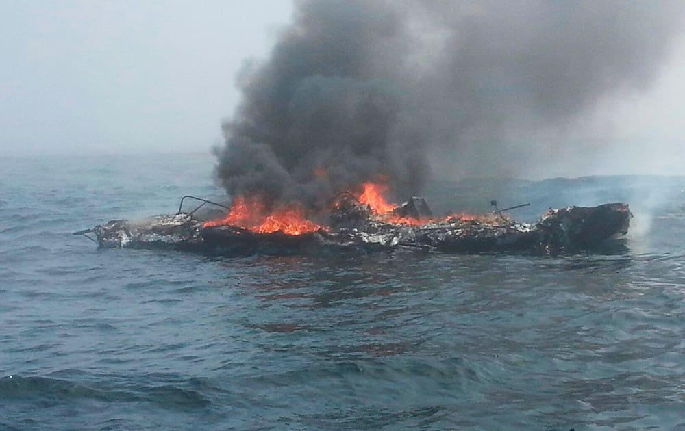 In this photo provided by the US Coast Guard, a 25-foot pleasure craft is engulfed in flames 3 miles north of Neah Bay, Wash.