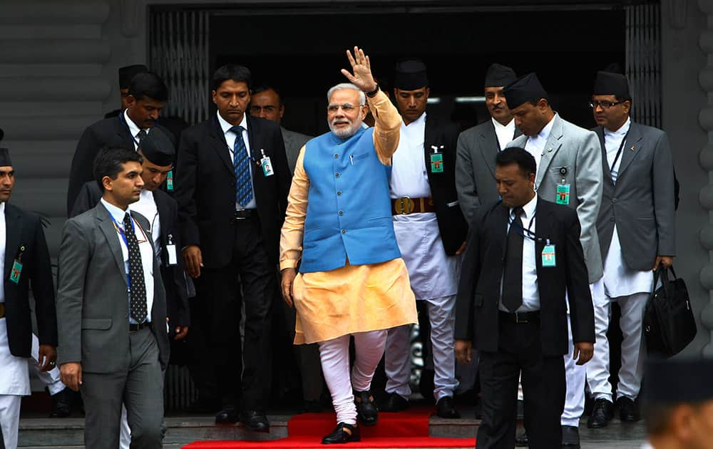 Indian Prime Minister Narendra Modi, center, waves to the media as he comes out after a meeting with his Nepalese counterpart Sushil Koirala, at the prime minister`s office in Katmandu, Nepal.