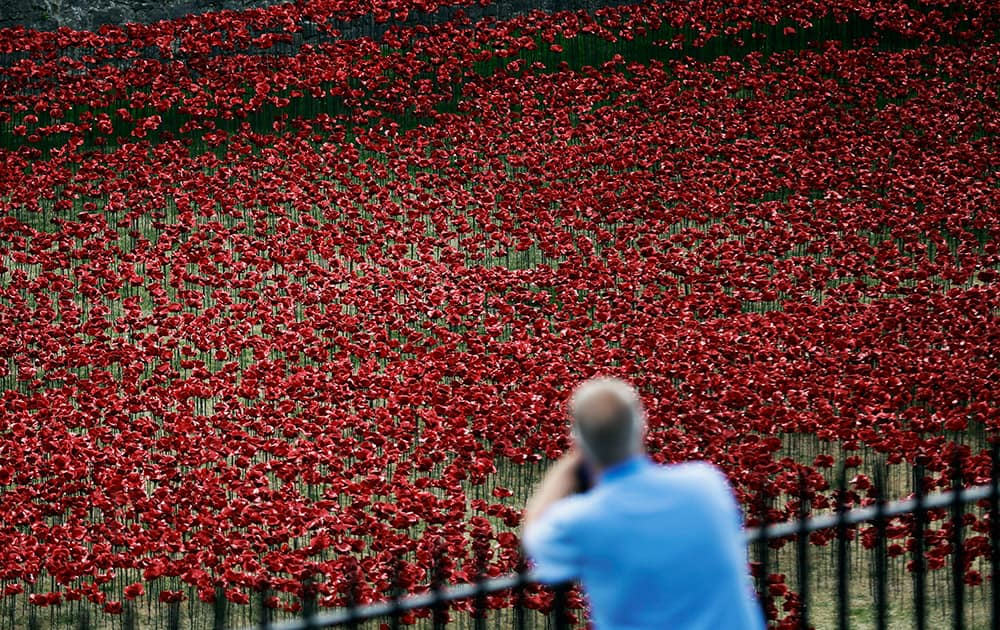 A man looks at ceramic poppies forming part of an art installation in the dry moat of the Tower of London in London. The installation of 888,246 ceramic poppies by ceramic artist Paul Cummins entitled `Blood Swept Lands and Seas of Read` will be unveiled on August 5 to mark the centenary of World War I, with the final one being planted on Armistice Day on November 11. Each poppy represents a British military fatality from World War I.
