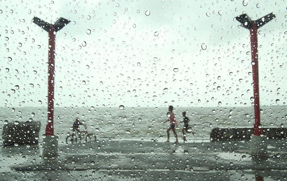 Filipino children play in the rain at a public park in suburban Navotas, north of Manila, Philippines.