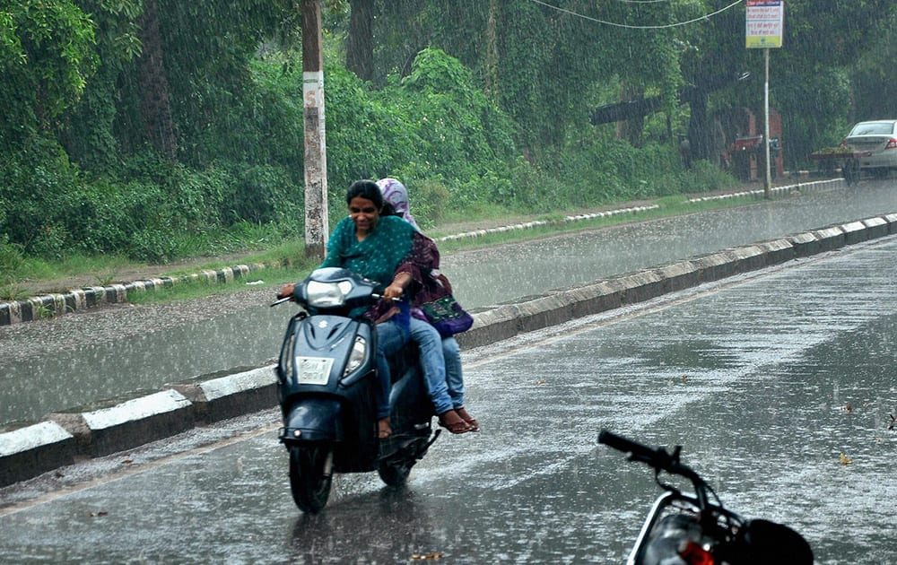 Girls riding a scooter in heavy rains in Patiala.