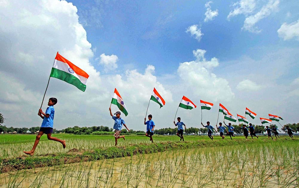 School children run with the Indian flags in a paddy field ahead of Independence Day at Parui in Birbhum district of West Bengal.