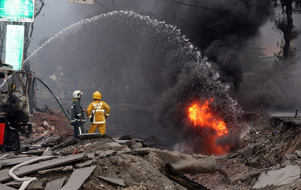 Firemen put out fire on the part of a destroyed street as fire continue to burn following multiple explosions from an underground gas leak in Kaohsiung, Taiwan.