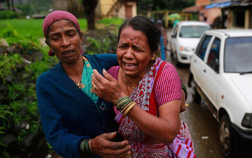 Women wail after seeing the body of a relative, victim of a landslide, in Malin village in Pune district of the western Indian state of Maharashtra.