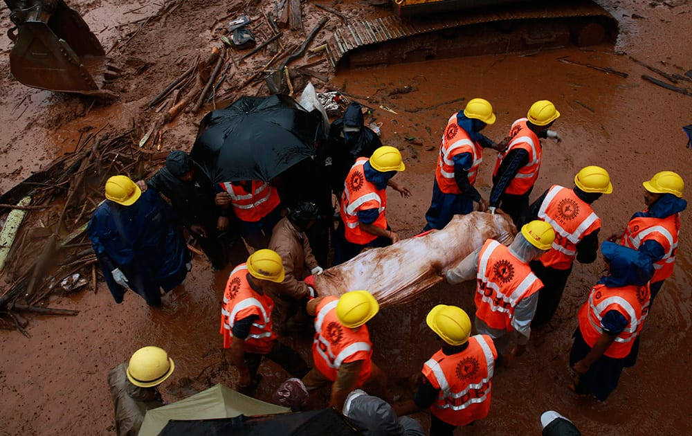 Rescue workers carry the body of a victim after a massive landslide in Malin village in Pune district of western Maharashtra state.