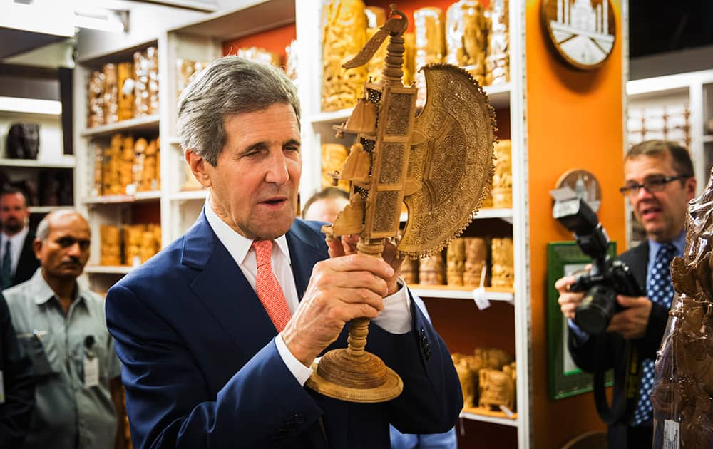 US Secretary of State, John Kerry, looks at a carved figurine during a visit to the Central Cottage Industries Emporium in New Delhi.