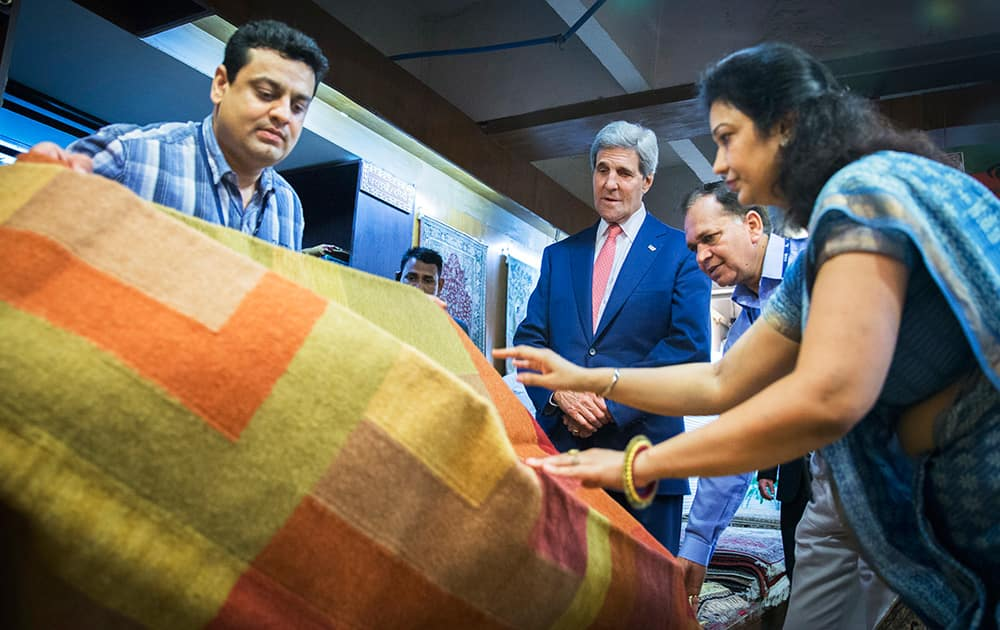 US Secretary of State, John Kerry, looks at carpets during a visit to the Central Cottage Industries Emporium in New Delhi.