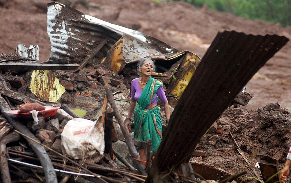 An elderly Indian woman cries as she searches for surviving family members in the debris of her home, destroyed by landslide in Malin village, in the western Indian state of Maharashtra.