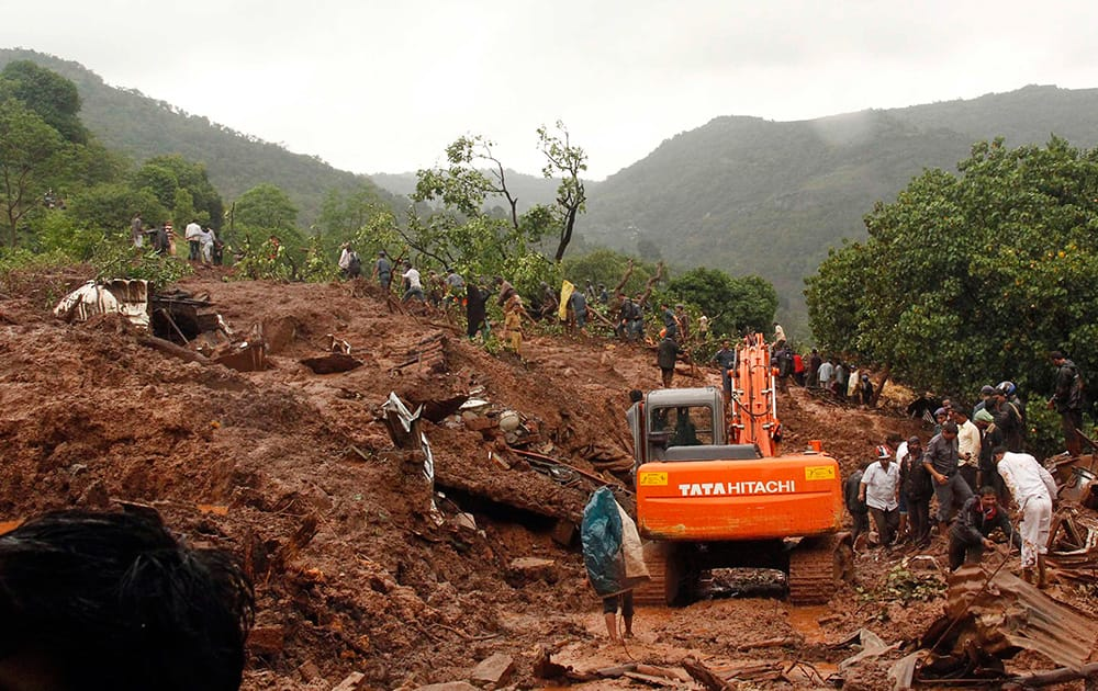 Rescue workers clear the debris at the site of a landslide in Malin village, in the western Indian state of Maharashtra.