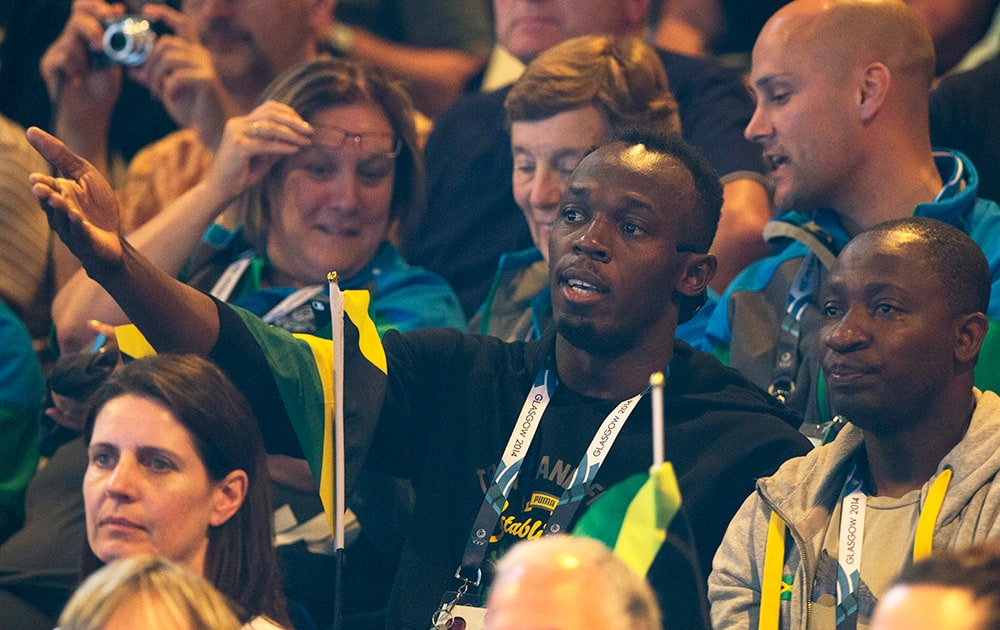 Double Olympic champion Usain Bolt of Jamaica, centre, watches the women`s pool A netball match between Jamaica and New Zealand at the Commonwealth Games Glasgow 2014, in Glasgow, Scotland.