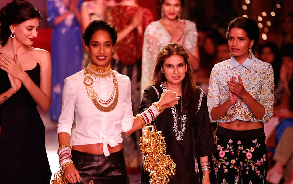 Indian designer Monisha Jaising, third from left, is led out by a model after a fashion show displaying dresses created by her at the India Couture Week, held by Fashion Design Council of India, in New Delhi.