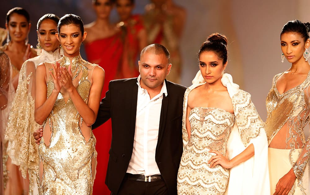 Designer Gaurav Gupta poses with models after a fashion show displaying dresses designed by him at the India Couture Week, held by Fashion Design Council of India, in New Delhi.