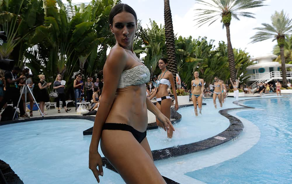 Models walk in a pool wearing swimwear designed by Poko Pano during the Mercedes-Benz Fashion Week Swim show in Miami Beach, Fla.