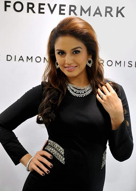 Actress Huma Qureshi poses with a diamond jewellery during a promotional event in Bengaluru.