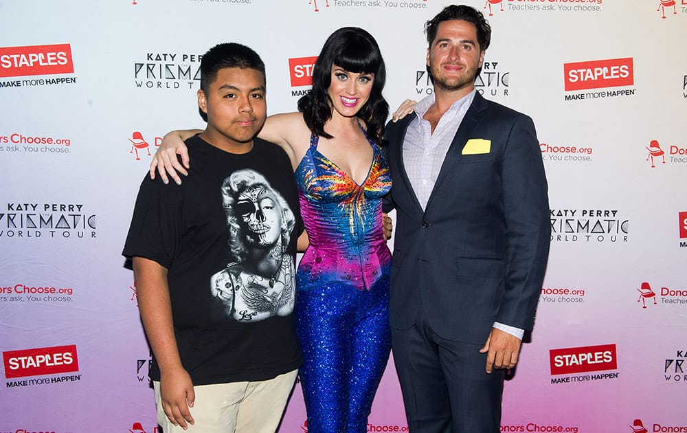 Global pop star Katy Perry, center, and local teacher and student from JHS 88 Peter Rougeet, left to right, Alex Martinez and Michael Seymour meet backstage at the Barclays Center during her Prismatic World Tour performance in Brooklyn, N.Y.