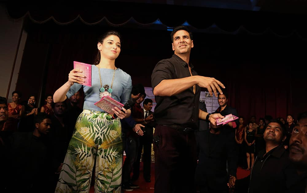 Bollywood actors Akshay Kumar, right, and Tamannaah Bhatia throw compact discs of songs from their upcoming movie 'Entertainment' during an promotional event at a college in Bangalore, India.
