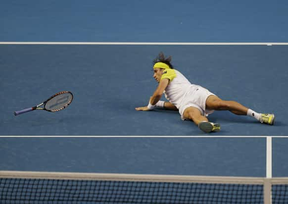 Spain's David Ferrer falls to the court during his first round match against Belgium's Oliver Rochus at the Australian Open tennis championship in Melbourne.