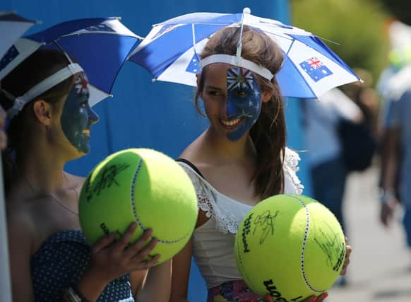 Spectators watch first round match on the outside courts at the Australian Open tennis championship.