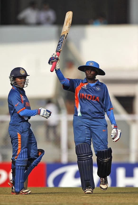 India's Thirush Kamini Murugesan raises her bat after scoring a century against West Indies during the opening cricket match of the ICC Women's World Cup in Mumbai.