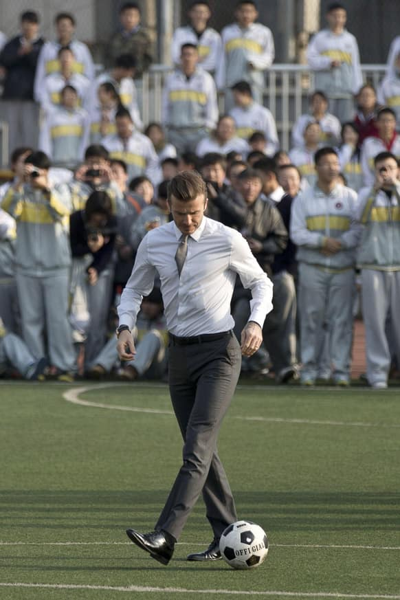 David Beckham, in his suit, plays soccer with students of Beijing's No. 2 High School during an event to promote the sport in China.