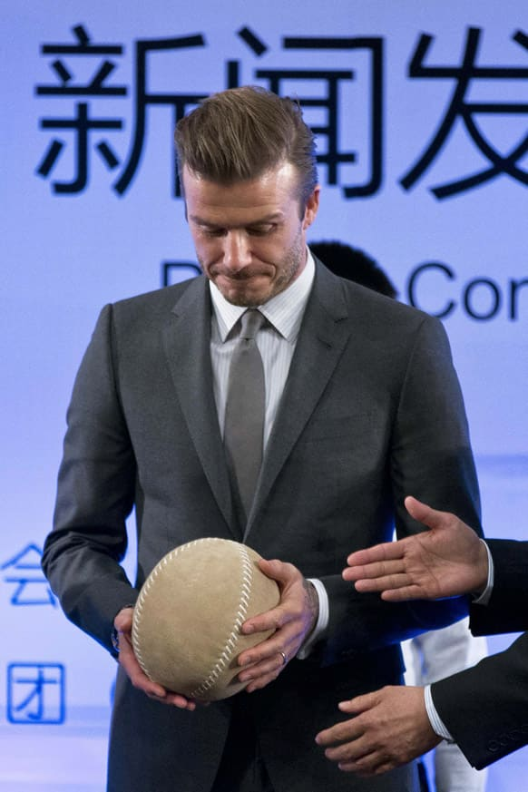 David Beckham is given a cuju ball, an ancient Chinese ball game similar to soccer, during a event to promote soccer games and Chinese soccer league at Shijia Primary School in Beijing.