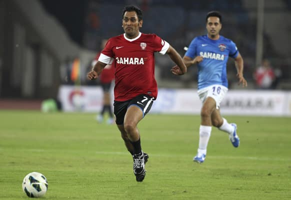 Mahendra Singh Dhoni, center, runs after a ball during a charity soccer match played between Indian cricket players and Bollywood actors in New Delhi.