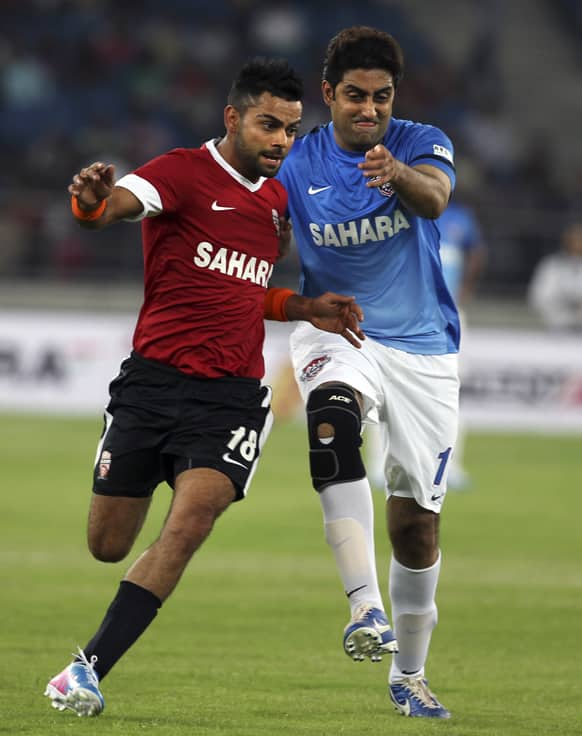 Virat Kohli and Bollywood actor Abhishek Bachchan vie for the ball during a charity soccer match played between Indian cricket players and Bollywood actors in New Delhi.