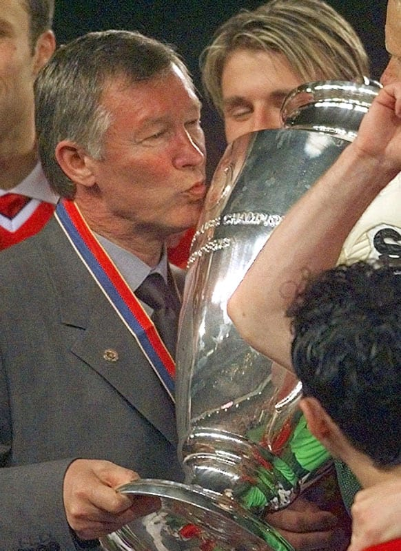 In this Wednesday, May 26, 1999 file photo Manchester United manager Alex Ferguson kisses the trophy after winning the Champions League final soccer match at the Nou Camp Stadium in Barcelona, Spain.