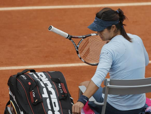 China's Li Na puts her racket away during a break because of light rain in the second round match against Bethanie Mattek-Sands of the U.S. at the French Open tennis tournament, at Roland Garros stadium in Paris. Mattek-Sands won in three sets 6-1, 5-7, 6-4.
