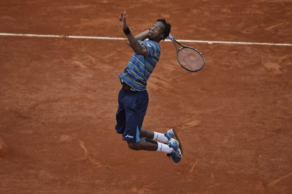 Gael Monfils of France jumps to return against Tommy Robredo of Spain in their third round match at the French Open tennis tournament, at Roland Garros stadium in Paris.