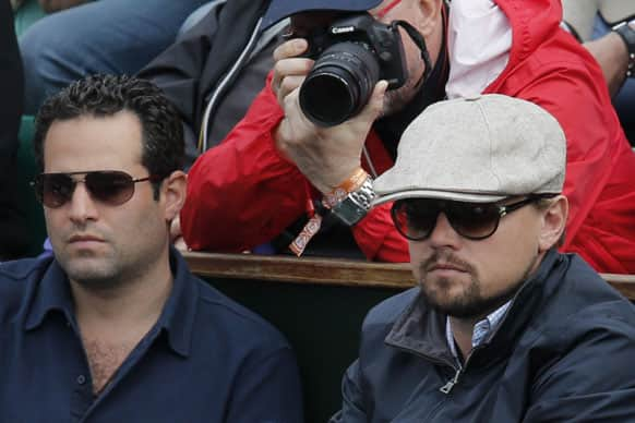 Actor Leonardo DiCaprio, right, watches the fourth round match of Switzerland's Roger Federer against France's Gilles Simon at the French Open tennis tournament, at Roland Garros stadium in Paris.