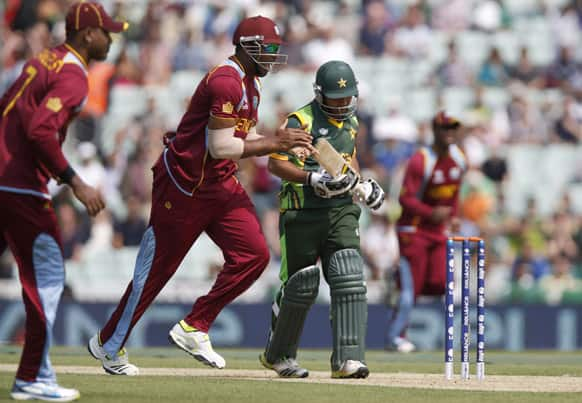 Pakistan's Asad Shafiq, right, walks off the crease as West Indies' players celebrate the wicket caught by Ravindranath Rampaul during their ICC Champions Trophy group B cricket match at the Oval cricket ground in London.