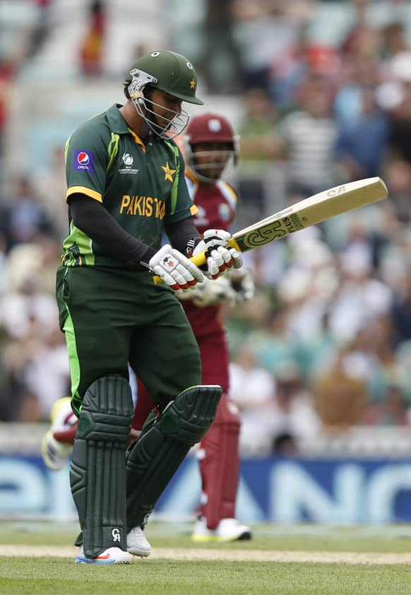 Pakistan's Nasir Jamshed walks off the crease after caught by West Indies' Ravindranath Rampaul during their ICC Champions Trophy group B cricket match at the Oval cricket ground in London.