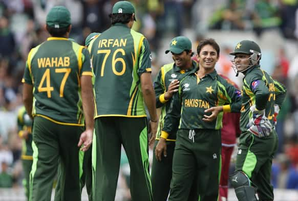 Saeed Ajmal celebrates his wicket of West Indies' Chris Gayle with teammates during their ICC Champions Trophy group B cricket match at the Oval cricket ground in London.