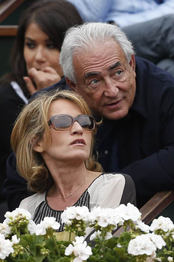 Former IMF Secretary General Dominique Strauss-Kahn, right, and his companion Myriam L'Aouffir watch Spain's Rafael Nadal playing compatriot David Ferrer during the men's final match of the French Open tennis tournament at the Roland Garros stadium.